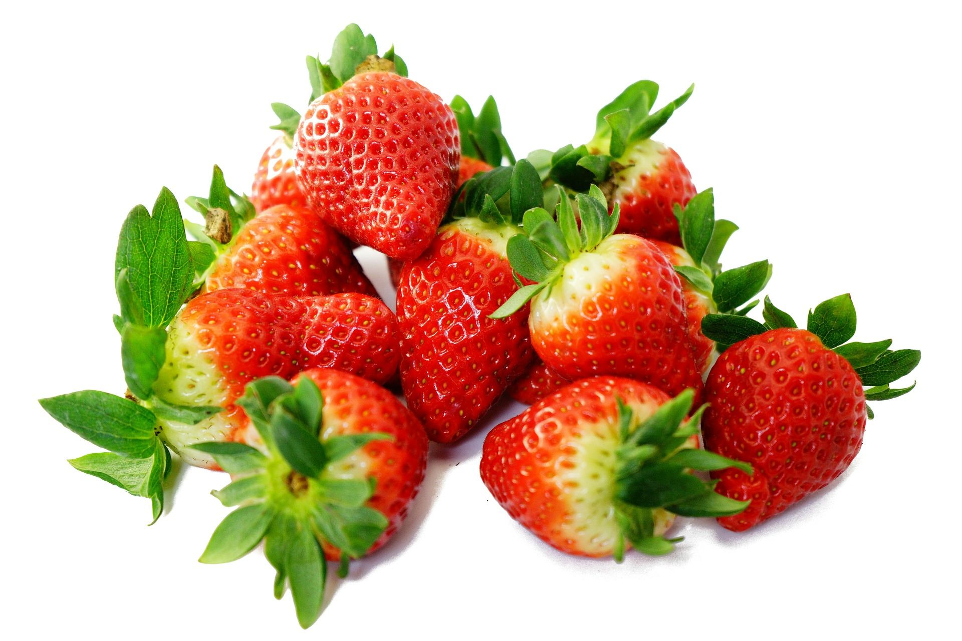 A pile of green and red strawberries